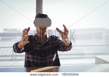 Young businessman using virtual reality headset in creative office