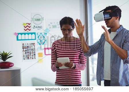 Female colleague assisting man while using virtual reality headset in office