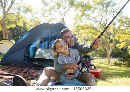 Father and daughter holding a fishing rod outside the tent while fly fishing