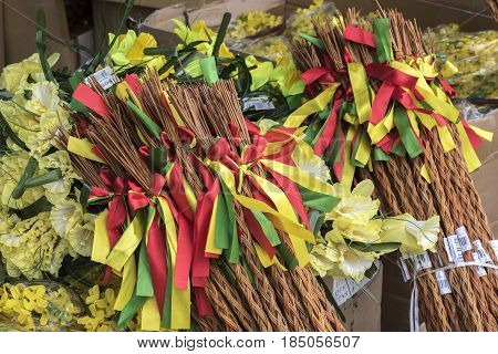 Easter sticks with red green and yellow ribons yellow easter flowers placed outside a shop.