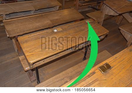 Old classroom with school desks and a green arrow. Concept Continuing education pass an exam the high school.