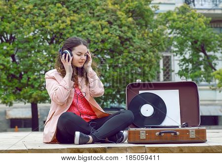 Young woman listening to music in a park. Portrait of girl feeling good with songs on old stereo vinyl system.