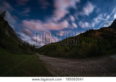 The Starry Sky With Blurred Motion Colorful Clouds And Bright Moonlight. Expansive Night Landscape I
