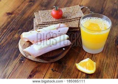 Wooden cutting board with crispbread, cheese, ham, cherry tomato, glass of fresh orange juice on a wooden background. Healthy breakfast. Healthy eating concept