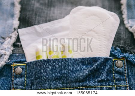 Close up shot of pocket of jeans with menstrual pads and packs.