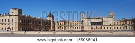 Gatchina Palace. Russia. Panoramic view of the Palace Square and the main entrance and the left wing of the palace with a watchtower. In the foreground - a monument to Paul.