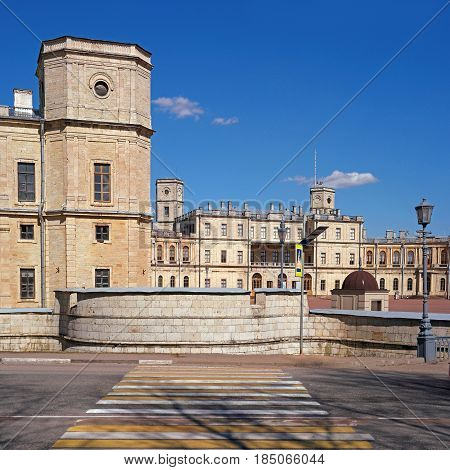 Gatchina Palace. Russia. Central building with balconies. In the foreground is the watchtower of the left wing, the palace is surrounded by a watery moat. The pedestrian crossing leads to the palace.