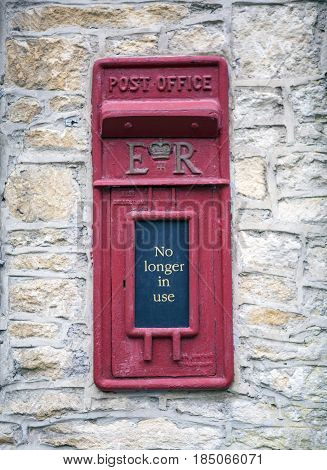 CASTLE COMBE UK - MAY 5 2017: Main street in Castle Combe Wiltshire UK showing old disused post office box