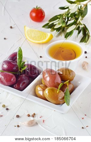 White plate with black and green olives with olive leaves on a white abstract background with lemon, cherry tomato, spices. Healthy food. Greek food. Mediterranean food