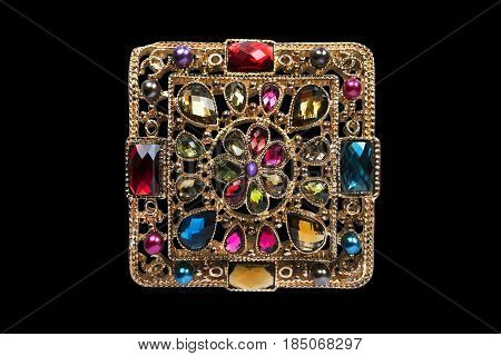 Vintage gold brooch with colorful gems isolated over black