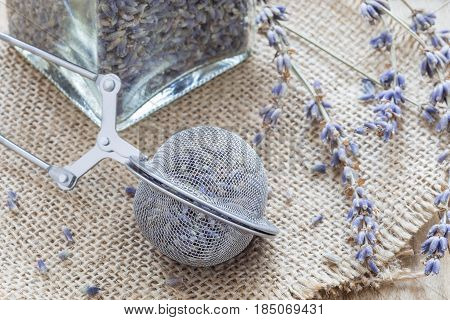 Dry lavender tea in tea infuser spoon and glass jag on wooden background horizontal closeup
