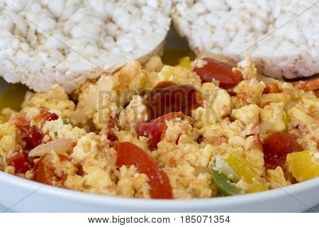 Close up macro of scrambled eggs. The breakfast dish has onion green and red peppers. Rice cakes to accompany the high protein meal.