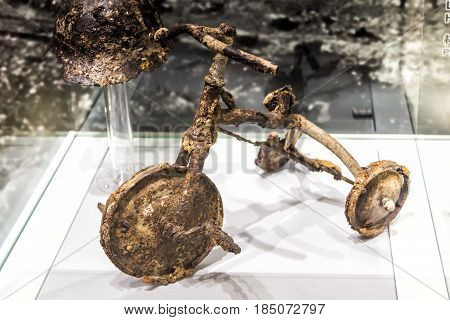 Hiroshima, Japan - April 28, 2014: The Shinichi Tetsutani tricycle exposed at the peace memorial Museum. Donated to the museum after buried for 40 years with Shinichi remains, a victim of the bomb