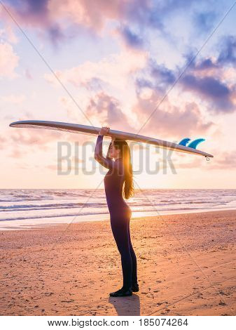 View of beautiful young woman surfer girl in wetsuit with surfboard on a beach at sunset or sunrise