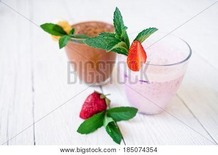 Blueberry smoothie with strawberry and chocolate and banana smoothie on white wood background. Fresh milkshake