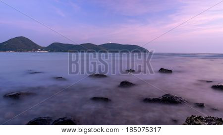 Long exposure of seascape with rock under blue sky in evening time.