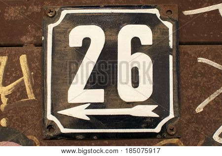 Weathered grunge square metal enameled plate of number of street address with number 26 closeup