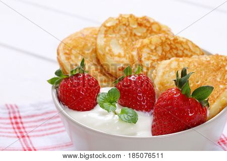 bowl of american pancakes with white yogurt and fresh strawberries on checkered dishtowel - close up