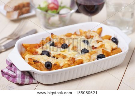 rigatoni pasta with olives and wine and salad
