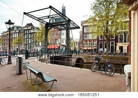 Amsterdam, Netherlands - April, 2017: Metal drawbridge on canal in Amsterdam city, Netherlands