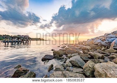 Rocky seashore with Wooden plank pier in beautiful morning sunrise at Khao Laem Ya National Park Rayong province Eastern Thailand