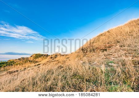 Beautiful rock mountain lanscape and dry grass meadow in bright blue sky at Khao Laem Ya National Park Rayong province Eastern Thailand