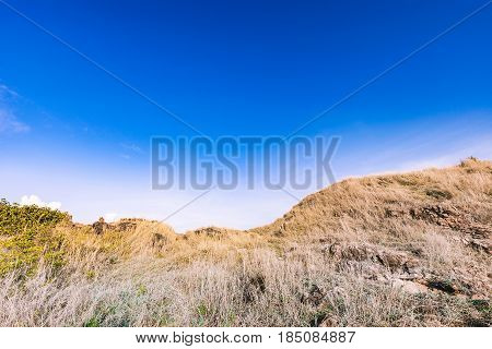 Beautiful rocks mountain lanscape and dry grass meadow in bright blue sky at Khao Laem Ya National Park Rayong province Eastern Thailand