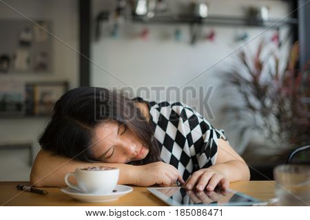 woman sleeping after reading book and drinking coffee on table at home or coffee shop or restaurant / woman sleeping