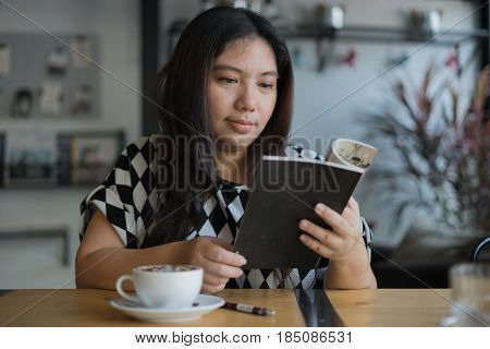 woman reading textbook relax sipping hot coffee happy at home or coffee shop or restaurant / woman reading book sipping coffee
