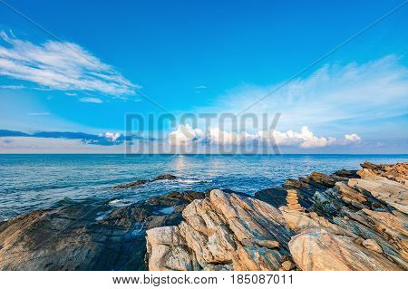 Rocky seashore in morning sunrise with bright blue sky and clouds at Khao Laem Ya National Park Rayong Province Eastern Thailand