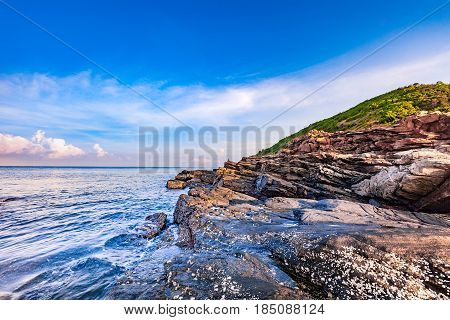 Rocky seashore canyon in morning sunrise with bright blue sky and clouds at Khao Laem Ya National Park Rayong Province Eastern Thailand