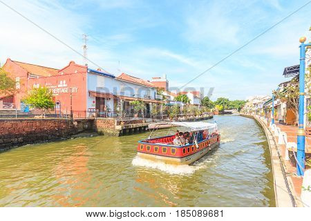 MALACCA, MALAYSIA - AUGUST 13, 2016: Cruise tour boat sails on the Malacca River in Malacca. Rehabilitation of the Malacca River to develop river tourism started in July 2002