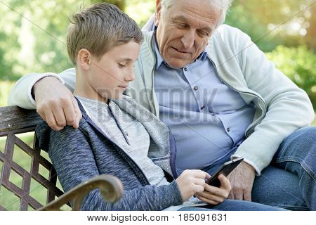 Portrait of ederly man with grandkid using smartphone