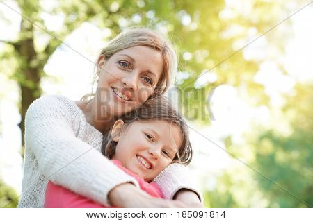 Portrait of mother and daughter sitting on bench outside