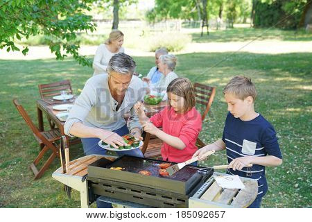 Man with kids cooking barbecue for the family