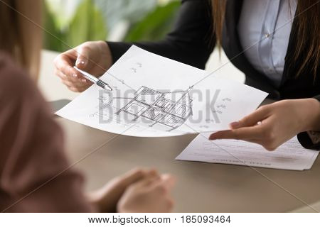 Close up view of female broker holding architectural house plan, signing lease agreement, meeting with realtor to find new home for rent, making deal with rental property in real estate agency