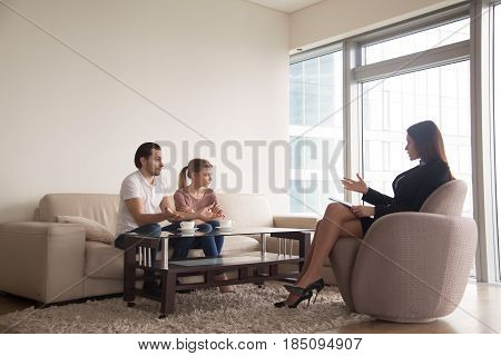 Family relationships expert trying to reconcile young arguing couple. Troubled husband blaming wife in problems in marriage while offended sad spouse sitting next to him during therapy session