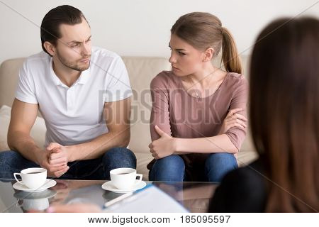 Young angry divorcing couple sitting on couch with arms crossed looking at each other with unconcealed hatred and hate, psychological help with problems in unhappy marriage, family counseling