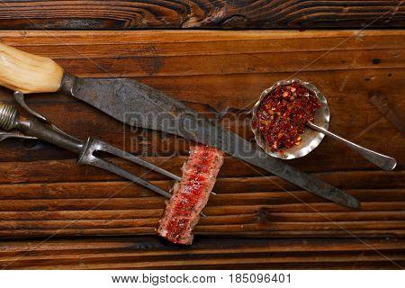 beef steak Slice on vintage meat fork  with dark wooden background