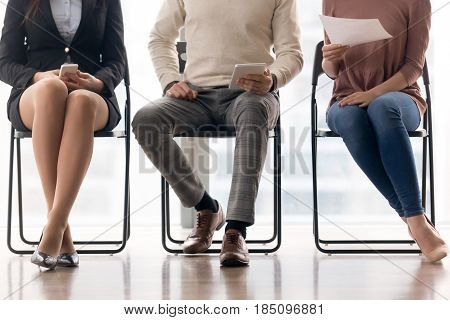 Three job applicants waiting for job interview sitting on chairs, man and two women preparing for audition, people in queue, audience of viewers on business training during break, human legs close up