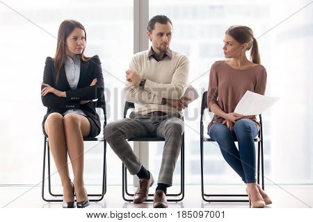 Male and female ambitious job seekers waiting for interview, looking at each other with hate and dislike, feeling jealous envious, rivalry and internal competition, get position and sidestep rivals