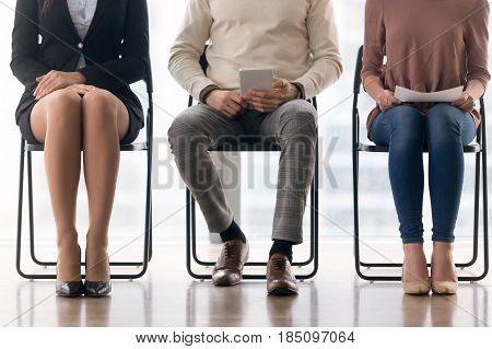 Three candidates for position waiting for their turn in job interview sitting on chairs, preparing for meeting, having audition, people in queue, human legs close up, job search concept