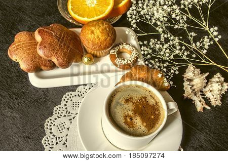 Koffee in white cup and saucer dishes with cakes and chocolatea saucer with orange slices on black table