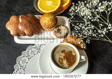 Koffee in white cup and saucer dishes with confectionery cakesa saucer with orange slices on black wooden table