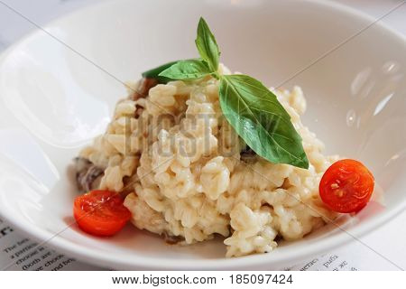 Creamy risotto in porcelain plate, toned image