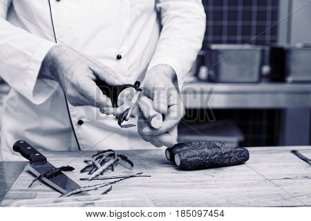 Chef is peeling cucumbers in restaurant kitchen, copy space, toned image