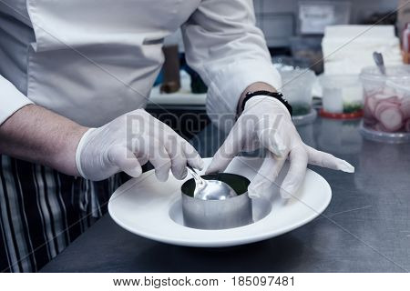 Chef in uniform is serving dish with metal ring at restaurant kitchen, toned image