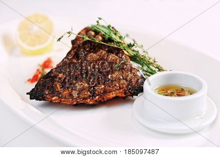 Grilled flounder (sole fish) with lemon, herbs and savory sauce, toned image
