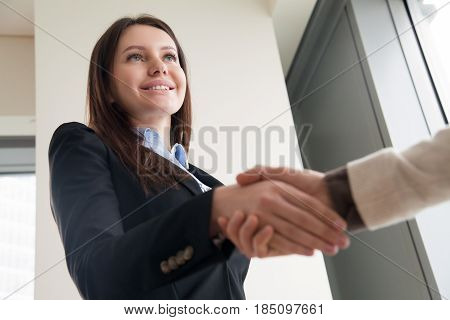 Portrait of beautiful young smiling businesswoman wearing suit shaking male hand, company director hiring female executive assistant, successful career girl is promoted and handshaking