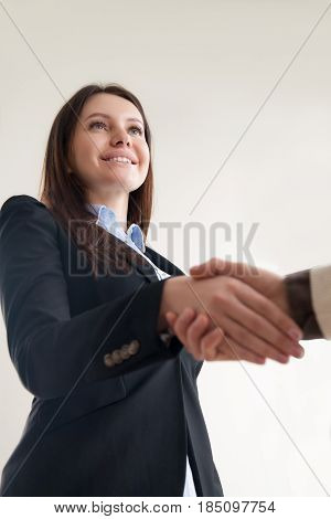 Beautiful smiling successful business lady shaking male hand, hr manager welcoming job applicant, female executive getting acquainted with new manager, nice to meet you, vertical view from below